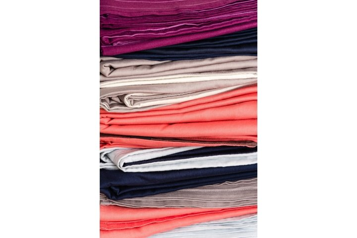 Stack of bed linen after laundry. Vertical background