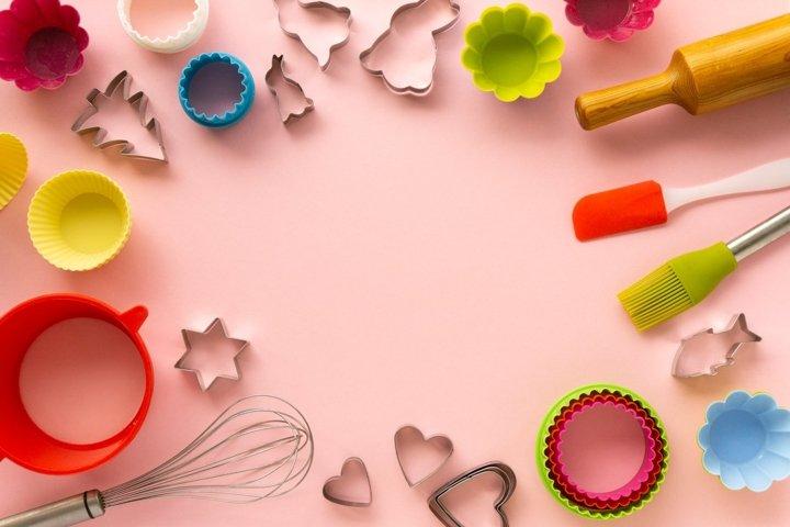 Frame of various baking utensils on pink background