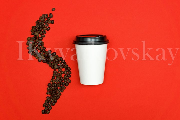 Top view of white paper dispocable coffee cup on red