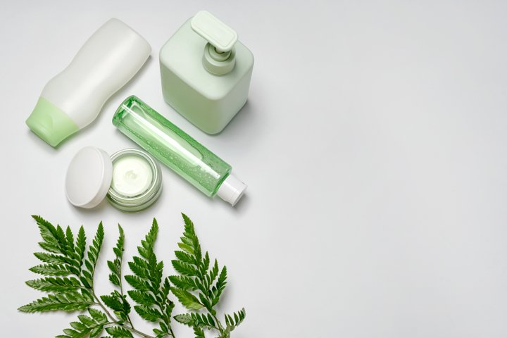 Cosmetic containers with green herbal leaves