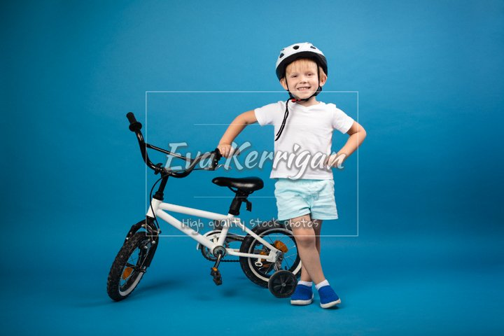 Child toddler with child bike and in protective helmet.