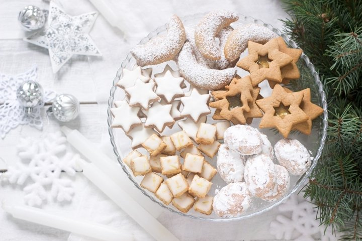 Various Christmas cookies on a transparent plate.