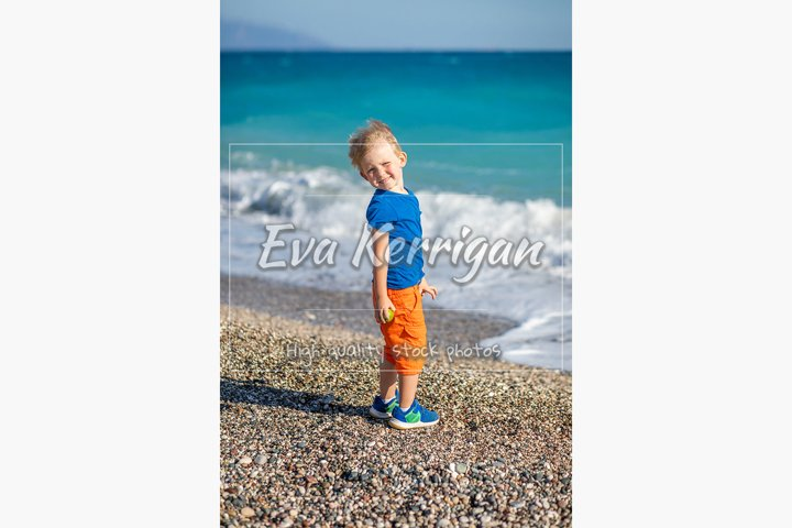 Child stands on beach of blue and turquoise sea of ocean.