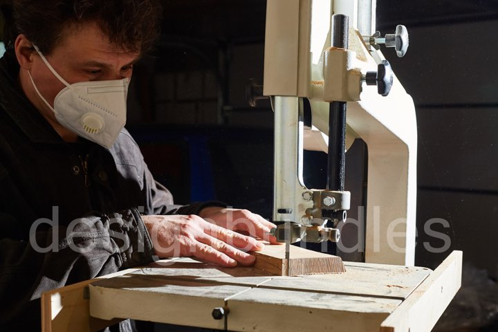 a man in a protective mask cuts a wooden board on a band saw