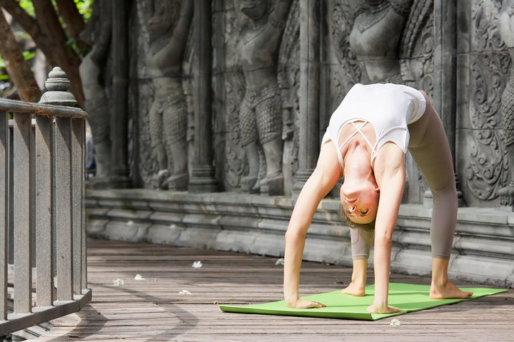 Woman doing yoga in abandoned temple on wooden platform