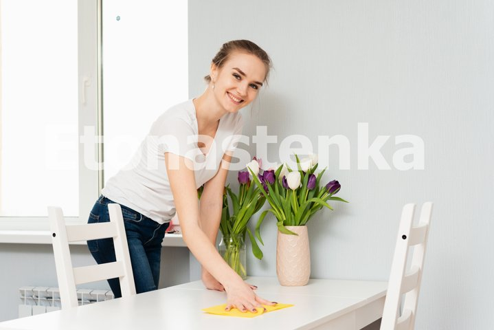 A cute blonde is smiling while cleaning her house