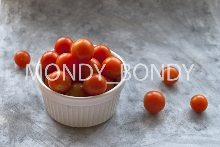 Red cherry tomatoes, white faceted plate, gray background