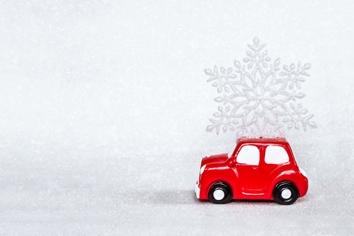 Red toy retro car delivering snowflake on the roof