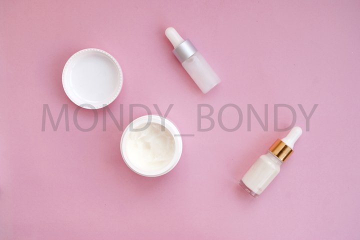 Open white bottle of thick coconut oil, cosmetics on a pink