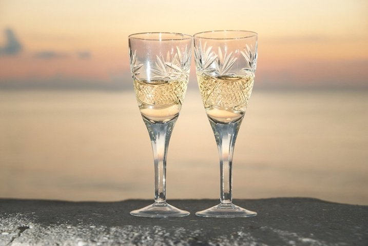 Two wedding glasses with champagne over sunset