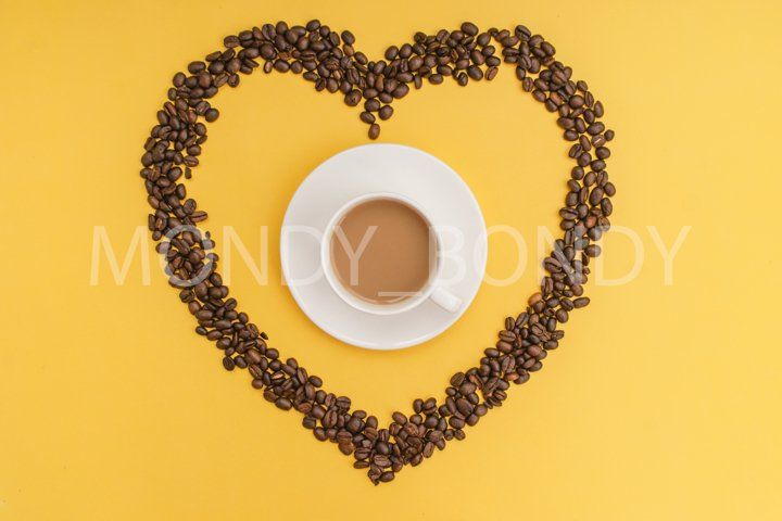White cup of coffee, heart shaped coffee beans