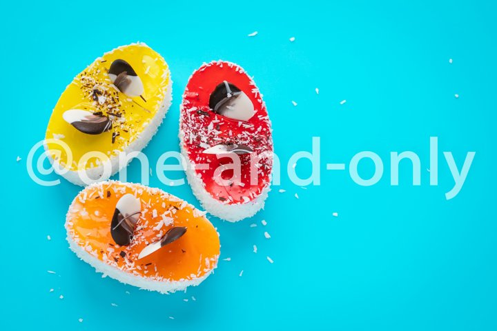 Multicolored cakes with coconut flakes on blue background.