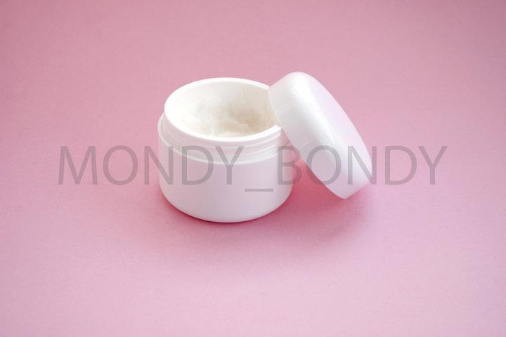White bottle of cream on a pink background. Flat lay.