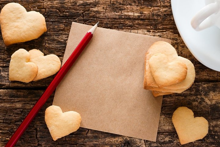 cookies in the shape of a heart, a cup of tea