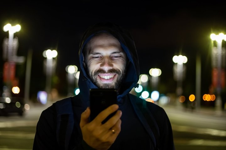 smiling man in the night city looks at the phone