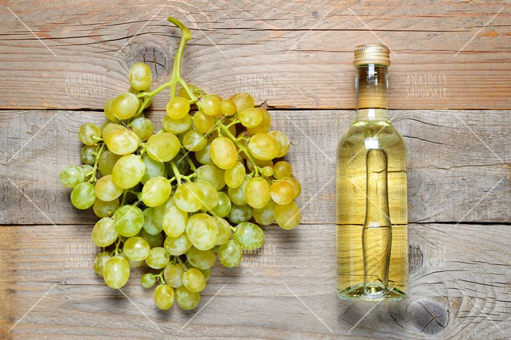 Small bottle of white wine and bunch of grapes