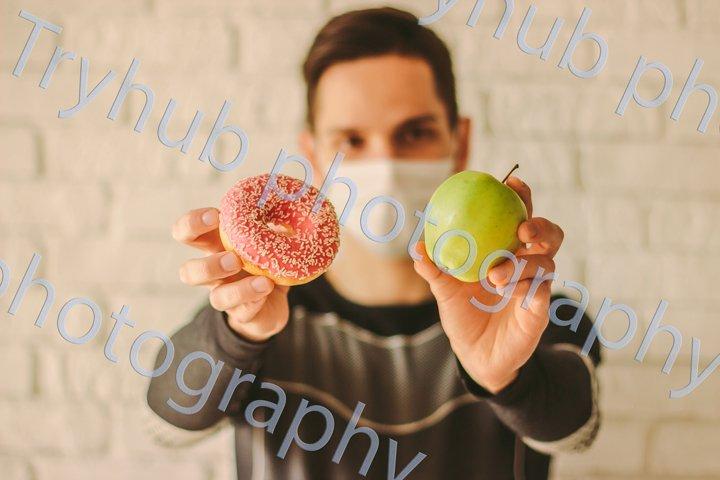 Sports man choosing between healthy apple or sugar donut