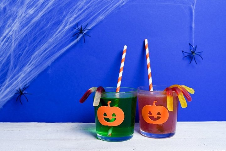 Colorful cocktails and decor for Halloween party on blue