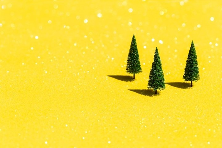 Fir trees on glittering yellow background with copyspace.