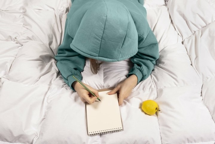Top view on a girl writing in a notebook from bed
