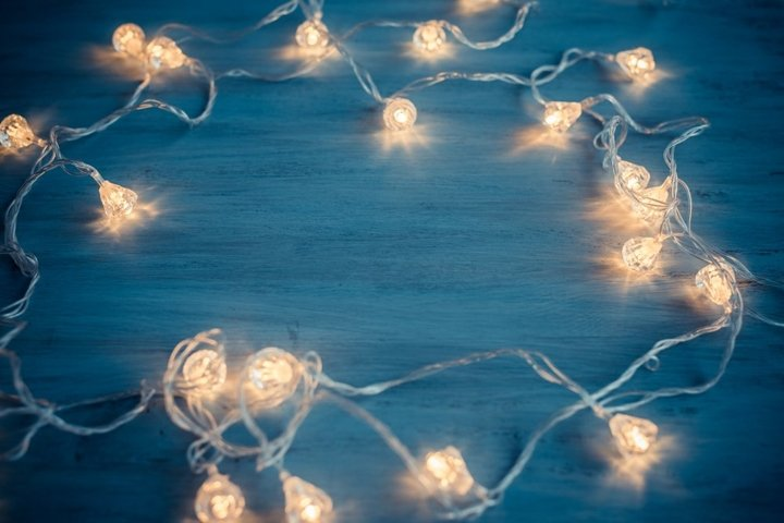Fairy lights frame on blue wooden christmas background