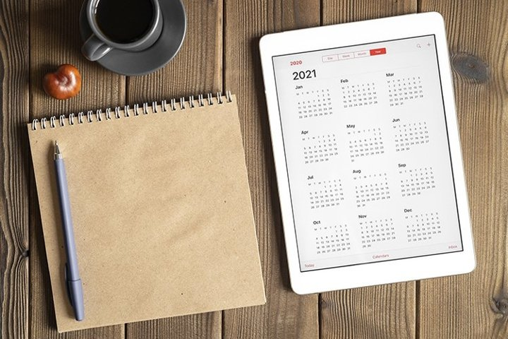 tablet with calendar for 2021, coffee, notebook, copy space