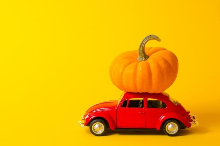 red toy car and orange pumpkin on the roof on yellow