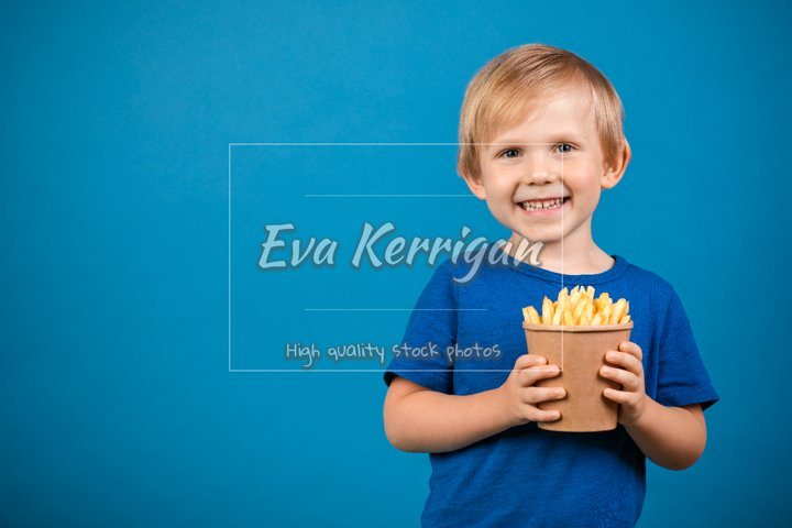 Boy blond child holding cup with fries in his hands.