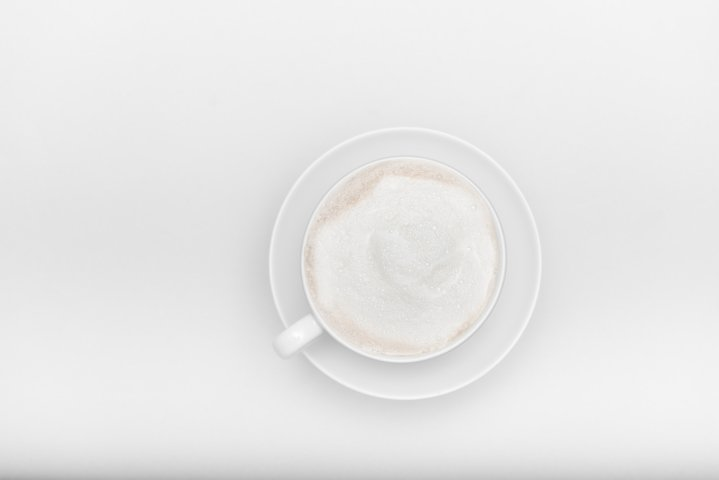 white cup with saucer and cappuccino on a white background