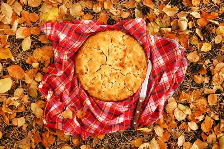 Top view on apple pie on the red checkered towel with knife.