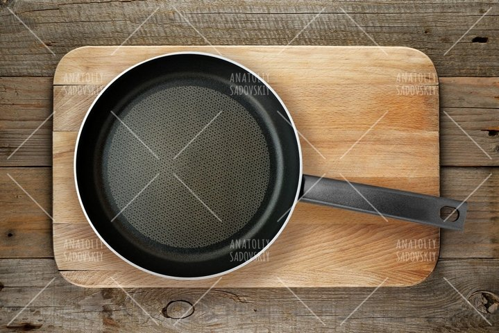 Empty frying pan on chopping board top view
