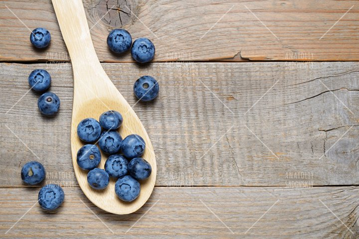 Blueberries in wooden spoon on table