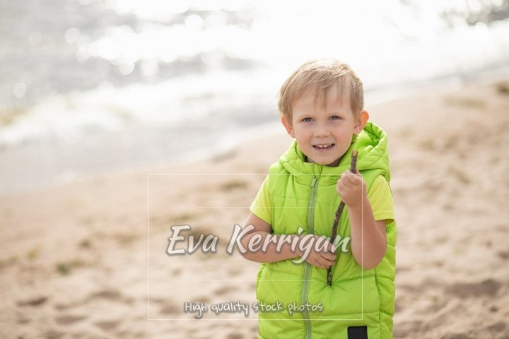 Blond boy on the beach on a background of sea and sand.