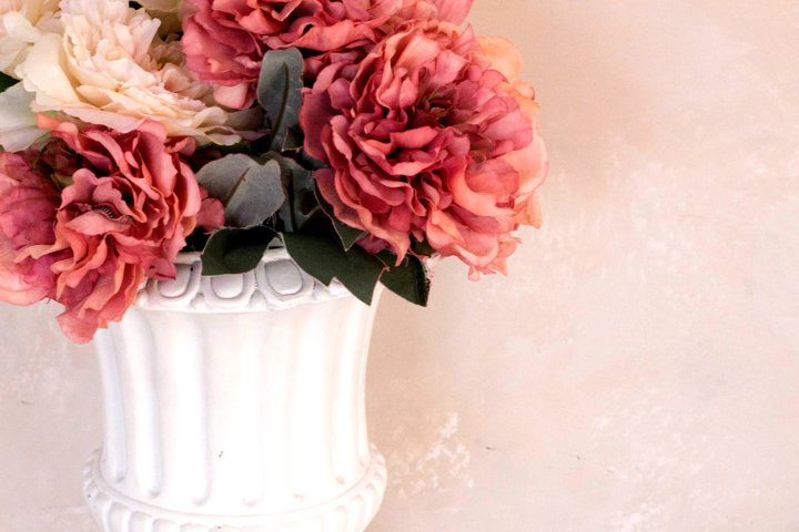Classic vase with flowers on a wall background