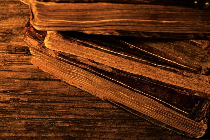 Stack of old worn leather-bound books on wooden background