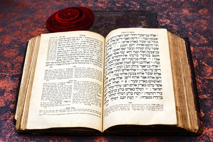 Jewish Bible. An open old Jewish book and red jewish bale