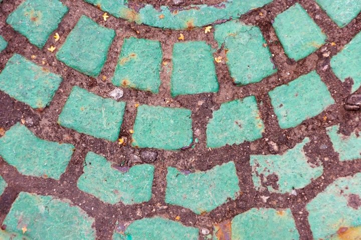 Closeup view on a green cobblestone road - circle pattern,
