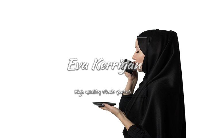 Muslim woman in black hijab with pleasure drinks coffee.