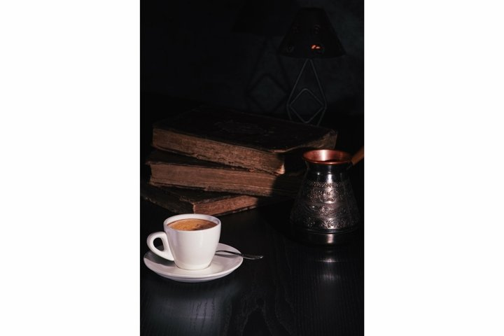 Cup of coffee, copper cezve on stack of old books in dark