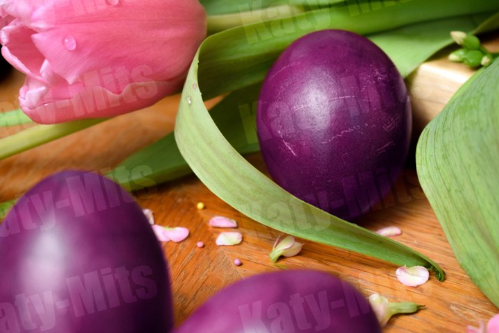 Violet Easter eggs on wooden table with pink flowers