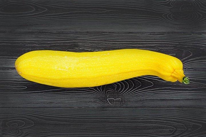 Yellow zucchini on a dark wooden background.