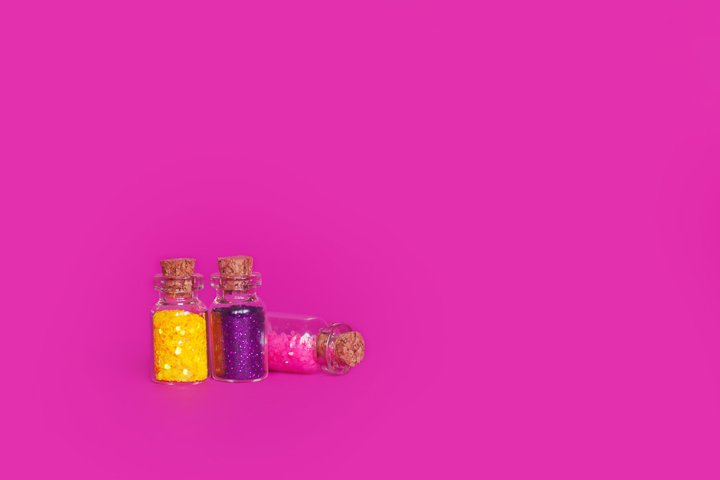 Colorful glitter in bottles on a bright pink background