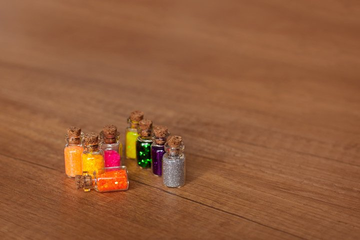 Colorful glitter in bottles on a wooden surface