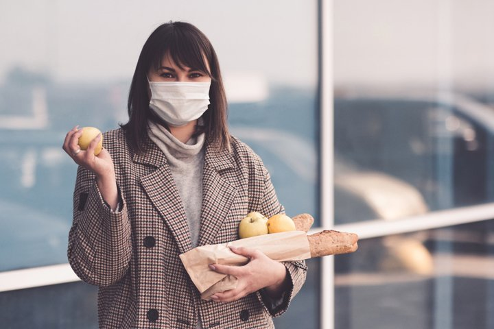 Woman wearing mask holding food