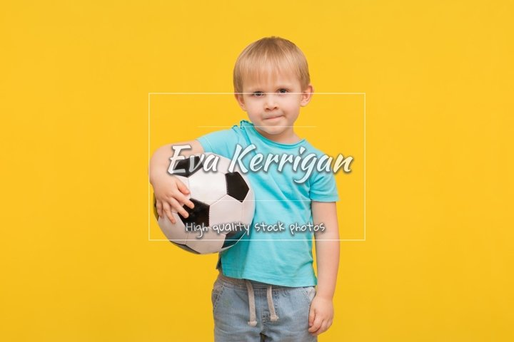 A boy stands with a soccer ball and looks at the camera.
