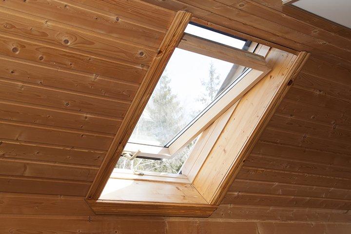 Open dormer window in wooden house in the attic