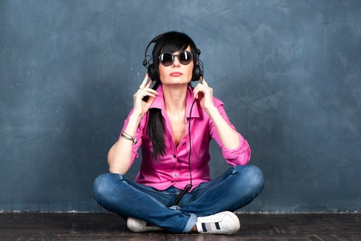 Trendy beautiful girl brunette DJ in headphones