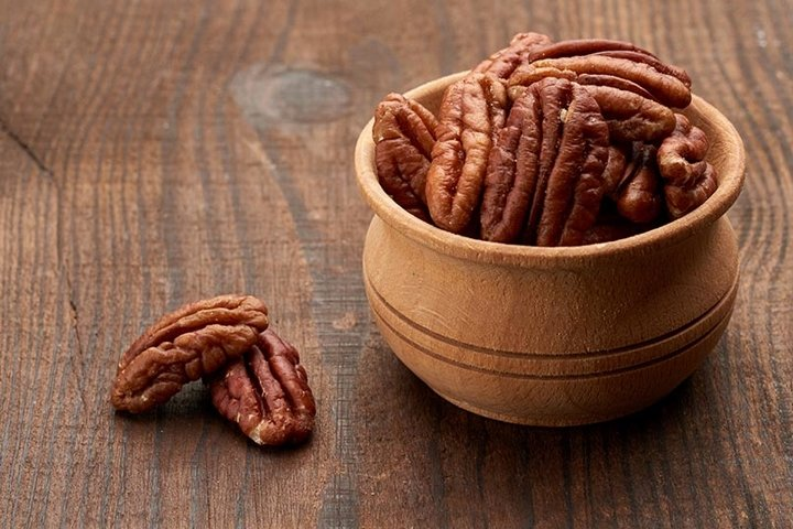 peeled pecans in a wooden plate on the table