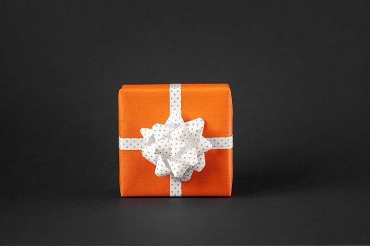 Orange present box with bow on black background.