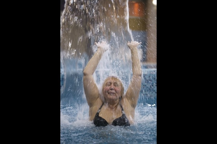 Woman splashing in a pool under a jet of water
